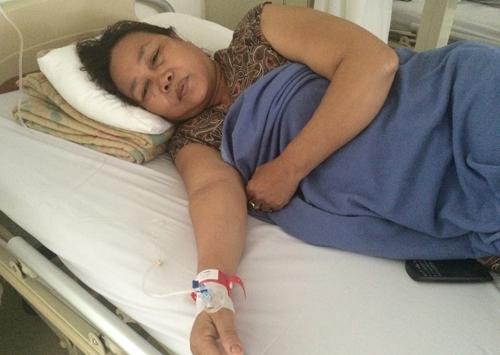 Do có tiền sử dị ứng thuốc, bà Xuân được đeo vòng tay thông tin màu đỏ. Ảnh: Lê Phương.