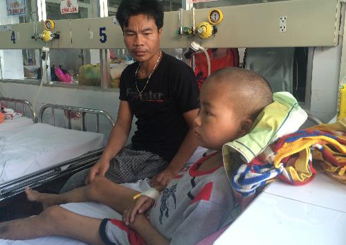 Sau hơn một tuần phẫu thuật, cậu bé hiện đã giảm đau đầu, vết mổ khô, có thể ngồi dậy. Ảnh: Lê Phương.