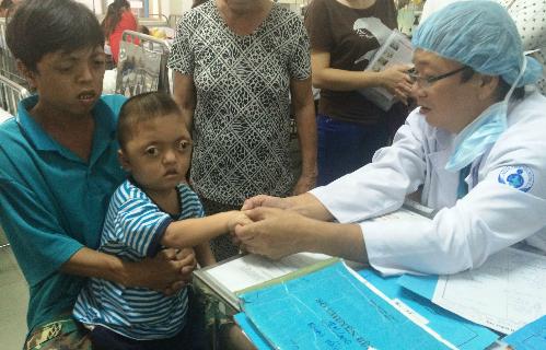 Anh Lạc và con trai lớn được bác sĩ kiểm tra dị tật 6 ngón. Ảnh: Lê Phương.
