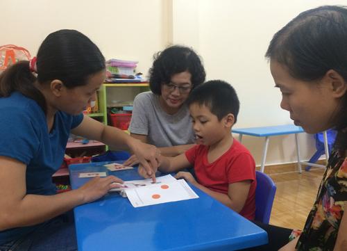 Bé Phong được bác sĩ và cô giáo hướng dẫn luyện tập. Ảnh: Lê Phương.