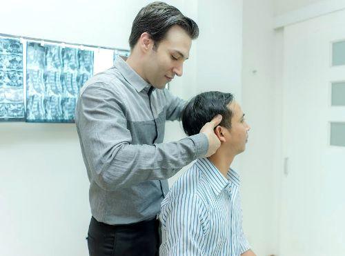 Bác sĩ Paul D'Alfonso đang nắn chỉnh cột sốngcho bệnh nhân bị bệnh lý ở cổ. Ảnh: TT.