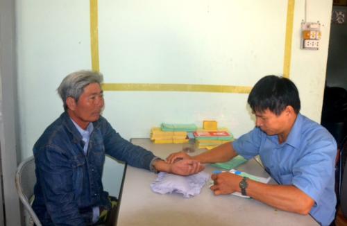 Anh Phạm Tường Huấn bắt mạch chẩn đoán bệnh cho bệnh nhân. Ảnh: Quỳnh Xuân.