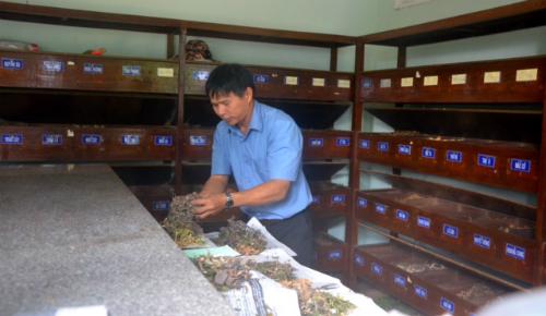Những loại thuốc được kê cho bệnh nhân đều được anh Huấn ghi cẩn thận trong toa và tự tay bốc thuốc vào giấy, gói cẩn thận trước khi đưa cho người nhận. Ảnh: Quỳnh Xuân