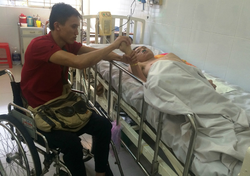 Đức ngồi xe lăn chăm sóc Linh ở bệnh viện. Ảnh: Lê Phương.