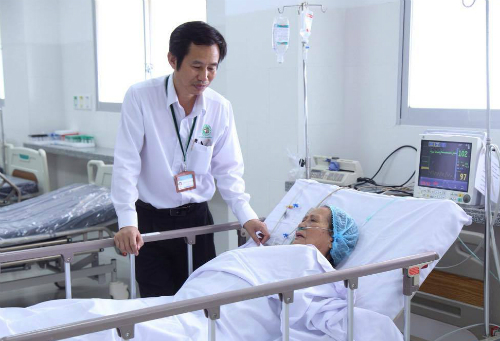 Bác sĩ Trần Văn Khanh thăm hỏi cụ bà ở phòng hồi sức. Ảnh: T.P