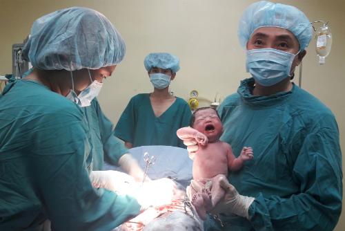 Bác sĩ đón em bé chào đời. Ảnh: P.T