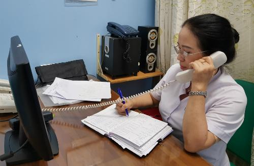 Chị Cúc tư vấn qua điện thoại cho người dân. Ảnh: Lê Phương.