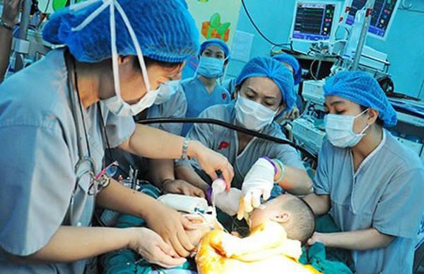 Ê kípcủa bác sĩ Tâm đang thao tác gây mê cho hai bé dính nhau vùng cùng cụt để chuẩn bị mổ tách. Ảnh: M.T.