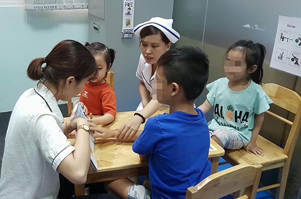 Giáo viên chuyên biệt và nhân viên y tế cùng phối hợp can thiệp trẻ tại phòng khám bác sĩ gia đình, Đại học Y khoa Phạm Ngọc Thạch. Ảnh: Lê Phương.