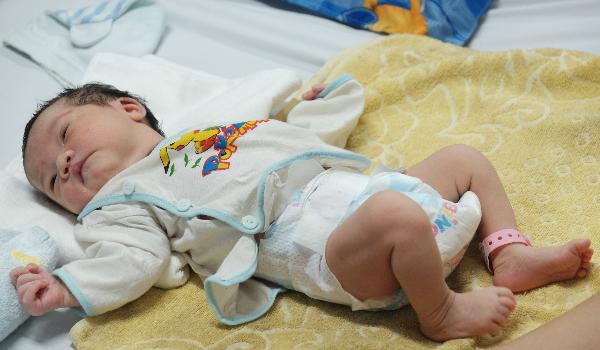 Mẹ không có sữa, những ngày đầu đời bé gái phải bú nhờ sữa của mọi người trong viện nhưng vẫn ngủ ngoan, không quấy khóc. Ảnh: Lê Phương.