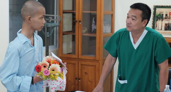 Tuấn Anh khỏe mạnh nhận hoa chúc mừng của các bác sĩ trong ngày xuất viện 25/6. Ảnh: Lê Phương.