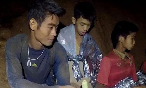 Huấn luyện viên Ekaphol Chantawong (trái) cùng các học trò trong hang Tham Luang. Ảnh: Hải quân Thái Lan.