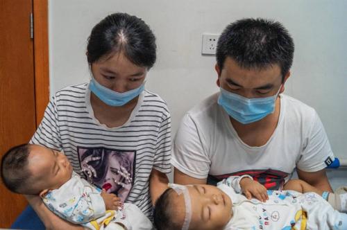 Cặp sinh đôi 10 tháng tuổi và bố mẹ. Ảnh: Quỹ Từ thiện Trẻ em Trung Quốc.