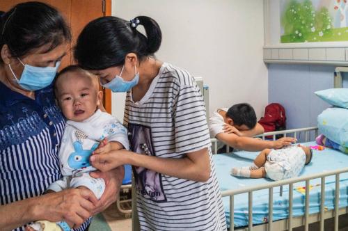 Bố mẹ hai bé quỵ ngã vì đau đớn. Ảnh: AsiaOne.