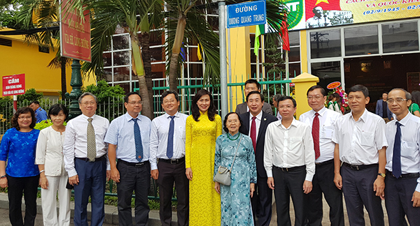 Phó chủ tịch UBND TP HCM Nguyễn Thị Thu (áo dài vàng) cùng gia đình viện sĩ Dương Quang Trung, các đại biểu dưới bảng tên đường mang tên thầy thuốc Dương Quang Trung. Ảnh: Lê Phương.