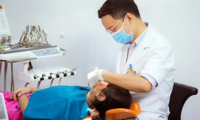 Theo bác sĩ Hoàng, cha mẹ cần tập cho trẻ thói quen chăm sóc răng miệng đúng cách từ khi còn bé: dùng chỉ nha khoa, chải răng, bỏ tật xấu như đẩy lưỡi, nghiến răng... Ảnh: T.P.