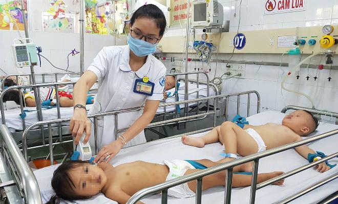 Điều dưỡng Huệ theo dõi trẻ bệnh tay chân miệng trong phòng cấp cứu Khoa Nhiễm, Bệnh viện Nhi đồng 1 ngày 5/10. Ảnh: Lê Phương.