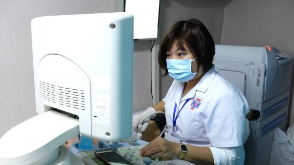 Bác sĩ siêu âm vú cho bệnh nhân trên xe lưu động. Ảnh: Lê Nga.