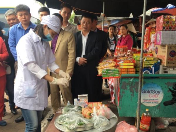 Nhân viên y tế test nhanh sản phẩm giò tại cổng đền Trần. Ảnh: Lê Nga.