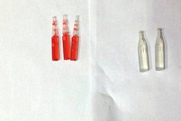 Lọ thuốc diệt chuột có chứa dung dịch màu đỏ.