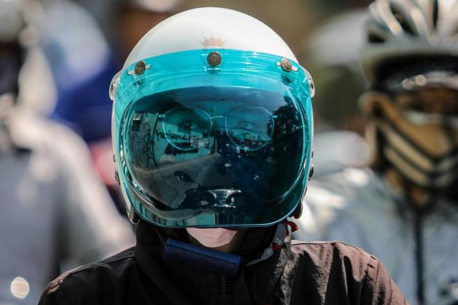 Cô gái mặc áo khoác, đội mũ bảo hiểm che kính kín mặt để chống nắng lúc giữa trưa trên đường ở TP HCM. Ảnh: Thành Nguyễn.