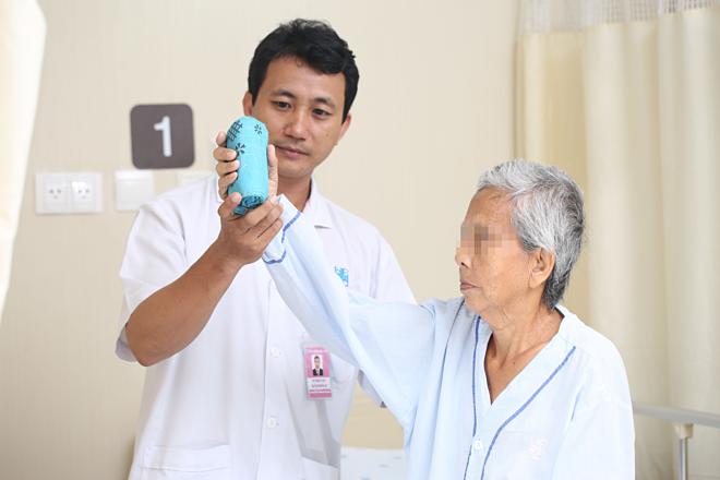 Kỹ thuật viên đang tập vật lý trị liệu phục hồi chức năng cho người bệnh. Ảnh: Bệnh viện cung cấp
