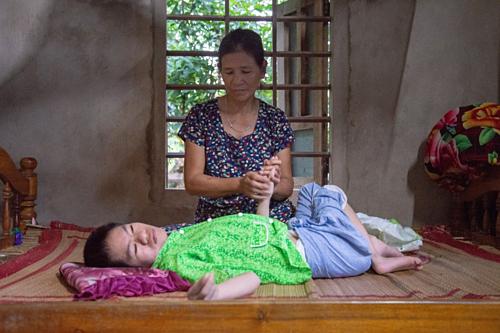 Bà Tran Thi Gai là người chăm sóc chính cho con gái Nguyen Thi Tai bị tổn thương não và loạn dưỡng cơ do chất độc da cam. Ảnh: Khairul Anwar.