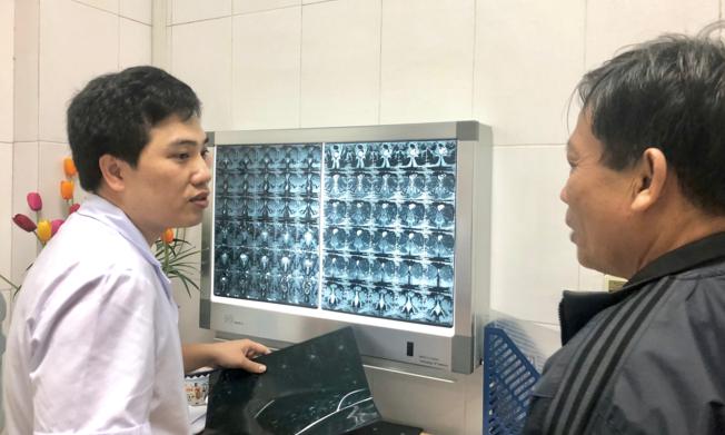 Bác sĩ Thịnh đang giải thích tình trạng bệnh nhân trên chụp phim. Ảnh: Thùy An
