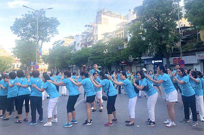 Anh Vinh hướng dẫn hơn 40 học viên cùng tập luyện các bài tập yoga cười ở Hồ Hoàn Kiếm sáng 13/7. Ảnh: Thùy An