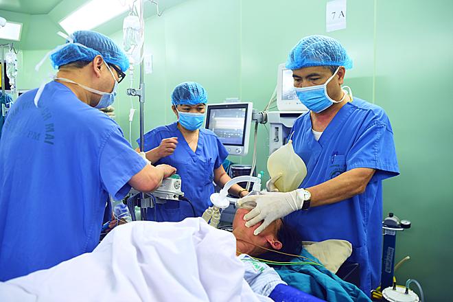 Bác sĩ Hào đang bóp bóng để cung cấp oxy cho bệnh nhân nữ bị K dạ dày. Ảnh: Giang Huy