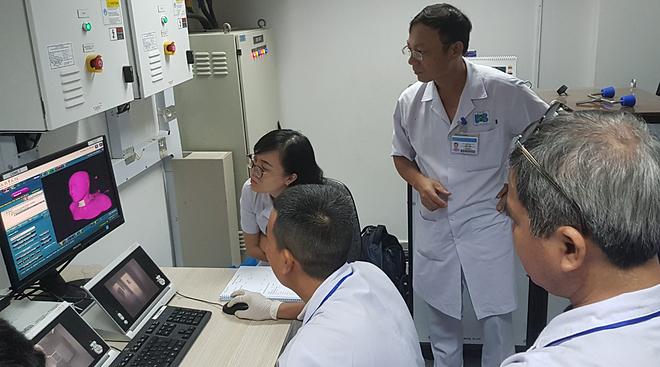Bác sĩ theo dõi quá trình xạ của bệnh nhân qua màn hình máy tính. Ảnh: Lê Phương.