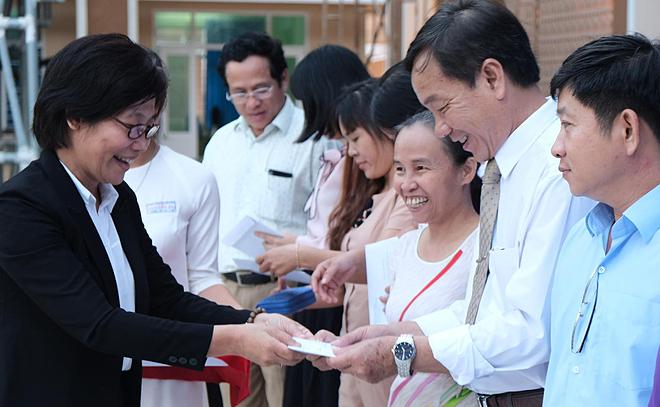 Bác sĩ Thu trao thẻ hiến tạng cho các thầy cô giáo trường THPT Nguyễn Du. Ảnh: T.C