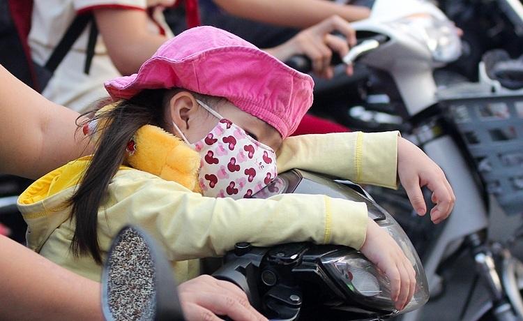 Một em bé ngủ gục trên xe máy của mẹ trong cảnh tắc đường ở TPHCM. Ảnh: Quỳnh Trần.