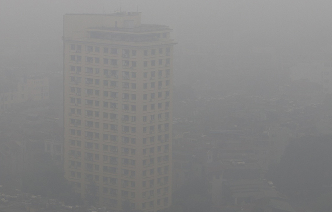 Các toà nhà cao tầng ở khu vực đường Trần Duy Hưng, đường vành đai 3 trên cao chìm trong màn sương mờ của bụi và sương mù sáng 13/12.Ảnh: Giang Huy.