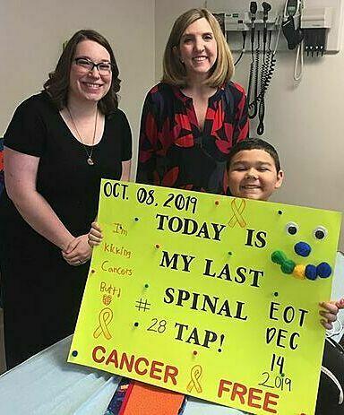 Steven Cotter cầm tấm bảng Hôm nay là ngày hóa trị cuối cùng của con. Ảnh: Ashley Cotter