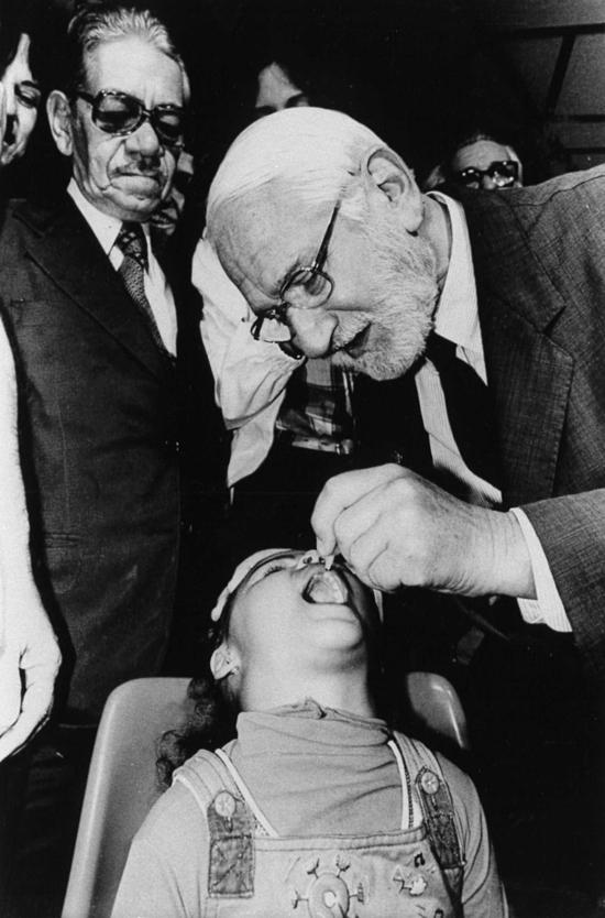 Tiến sĩAlbert Sabin cho trẻ uống vắcxin bại liệt. Ảnh:Pasteur Meriuex
