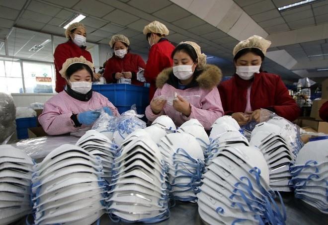 Chú thích ảnh là: Công nhân tại một nhà máy sản xuất khẩu trang ở Handan, Trung Quốc. Ảnh: EPA