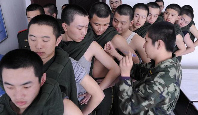 Cảnh sát bán quân sự Trung Quốc nhận vắcxin H1N1. Ảnh: Reuters