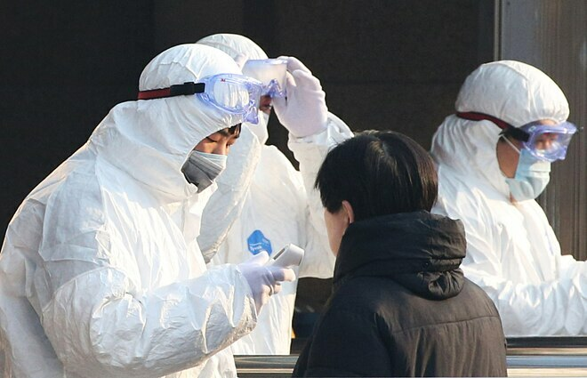Nhân viên y tế tiến hành kiểm tra nhiệt độ hành khách tại Sân ga Bắc Kinh. Ảnh: Reuters