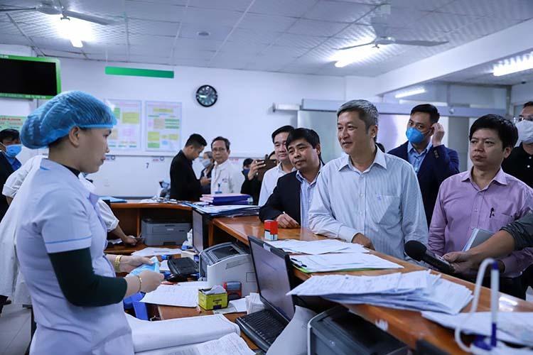 Thứ trưởng Bộ Y tế Nguyễn Trường Sơn hỏi chuyện điều dưỡng Lê Thị Như Ngọc về quy trình tiếp nhận bệnh nhân nghi nhiễm corona. Ảnh: Nguyễn Đông.