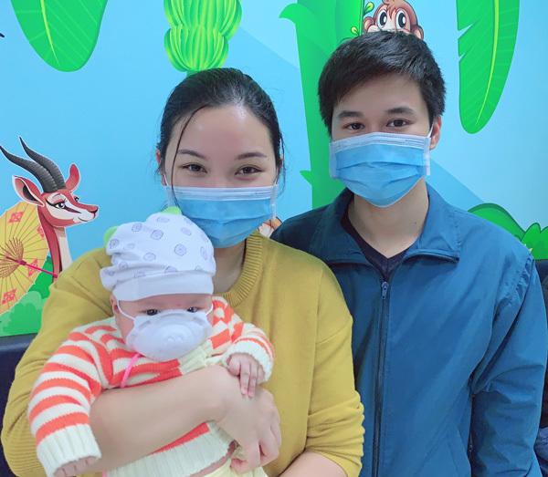 Một gia đình đưa con đi tiêm chủng theo lịch hẹn, dùng khẩu trang y tế để bảo vệ sức khoẻ cả nhà.