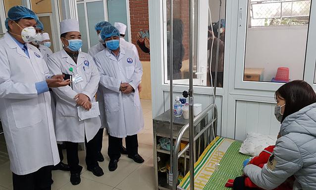 Thứ trưởng Đỗ Xuân Tuyên (trái) thăm bệnh nhân nghi ngờ mắc nCoV. Ảnh: V.T