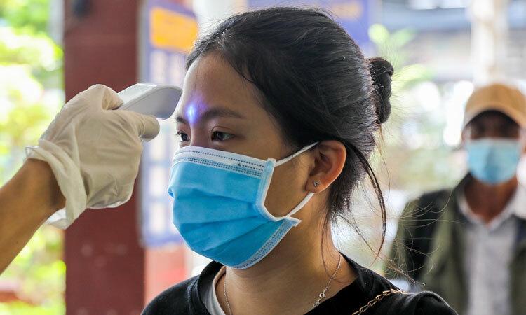Nhân viên y tế đo thân nhiệt cho hành khách trước khi rời ga Sài Gòn để phòng dịch bệnh đường hô hấp cấp do nCoV. Ảnh: Như Quỳnh.
