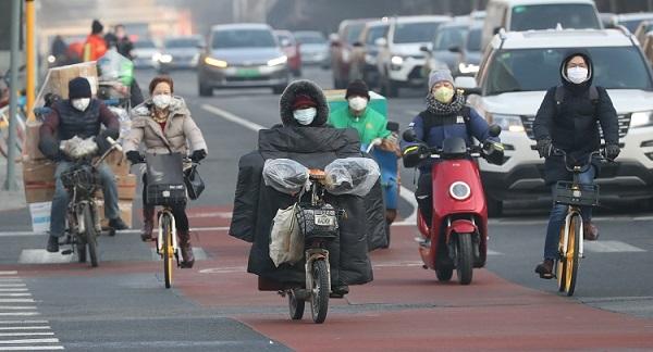 Công nhân và người lao động Bắc Kinh trên đường đi làm  sáng 10/2. Ảnh: Reuters