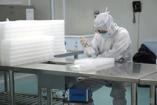 Bác sĩ tạitỉnh Quảng Đông đang tiến hành xét nghiệm mẫu bệnh phẩm viêm phổi corona. Ảnh: Reuters