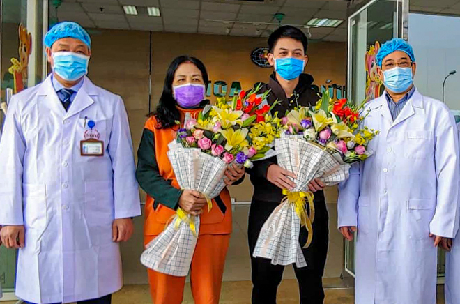 Hai bệnh nhân (giữa) ra viện sáng 18/1 tại Bệnh viện Bệnh Nhiệt đới Trung ương, Hà Nội. Ảnh: Thúy Quỳnh.