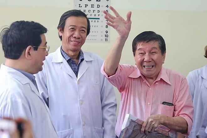 Bệnh nhân Tạ Hoa Kiênmặc áo hồng, tươi cười vẫy tay chào khixuất viện chiều 21/2. Ảnh: Hữu Khoa.
