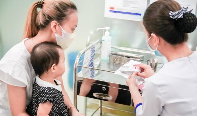 Một khách hàng đưa con đi tiêm tại trung tâm tiêm chủng VNVC vào sáng 21/2. Menactra được chỉ định cho trẻ từ 9 tháng tuổi đến 55 tuổi.
