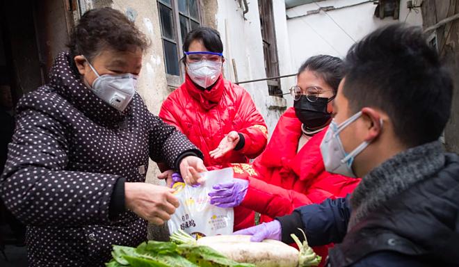 Tình nguyện viên tại Vũ Hán tiếp tế rau củ, lương thực cho một người phụ nữ. Ảnh: Xinhua