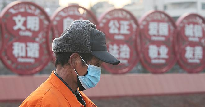 Người dân Bắc Kinh đeo hai lớp khẩu trang để phòng ngừa Covid-19. Ảnh: Reuters